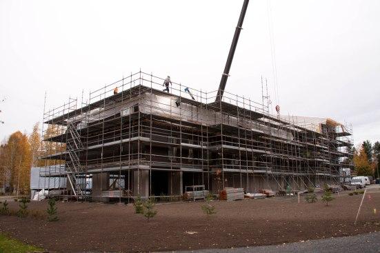 Suojamuovien alta paljastuu valmista julkisivua sitä mukaa kun uusia kerroksia saadaan päälle suojaksi.